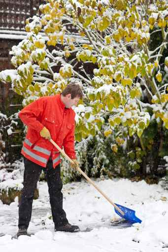 Adult man clean owns road to home against snow