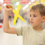 little boy holding yellow boomerang toy, standing in shop