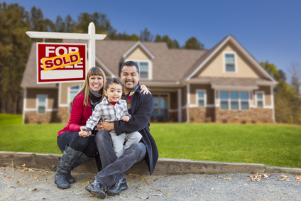 Happy Mixed Race Family in Front of Their New Home and a Sold For Sale Real Estate Sign.