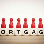 Mortgage concept: Red pawns on the word mortgage spelled