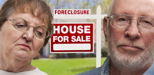 Depressed Senior Couple in Front of Foreclosure Real Estate Sign and House.