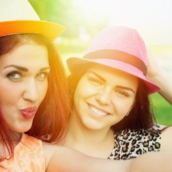 Two cute happy girlfriends taking a selfie outdoors in summer