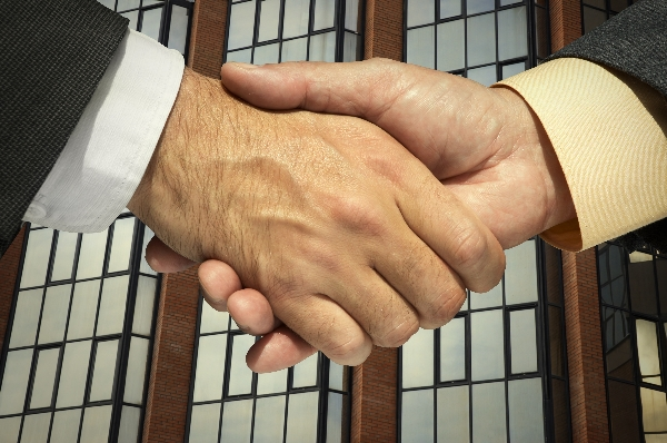 handshake  behind a corporative building.Great for any design.