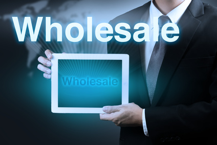 businessman holding tablet showing word WHOLESALE on virtual screen.