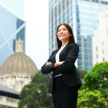 Businesswoman confident outside. Business woman standing proud and successful in suit cross-armed. Young multiracial Chinese Asian / Caucasian female professional in central Hong Kong.