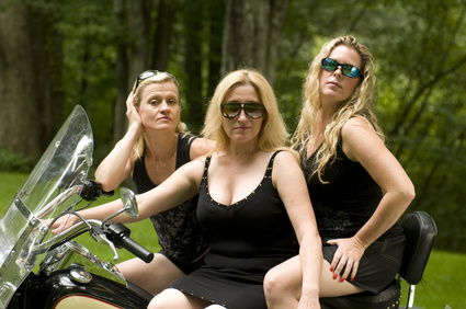 three sexy attractive middle age blond women on large motorcycle in black clothes