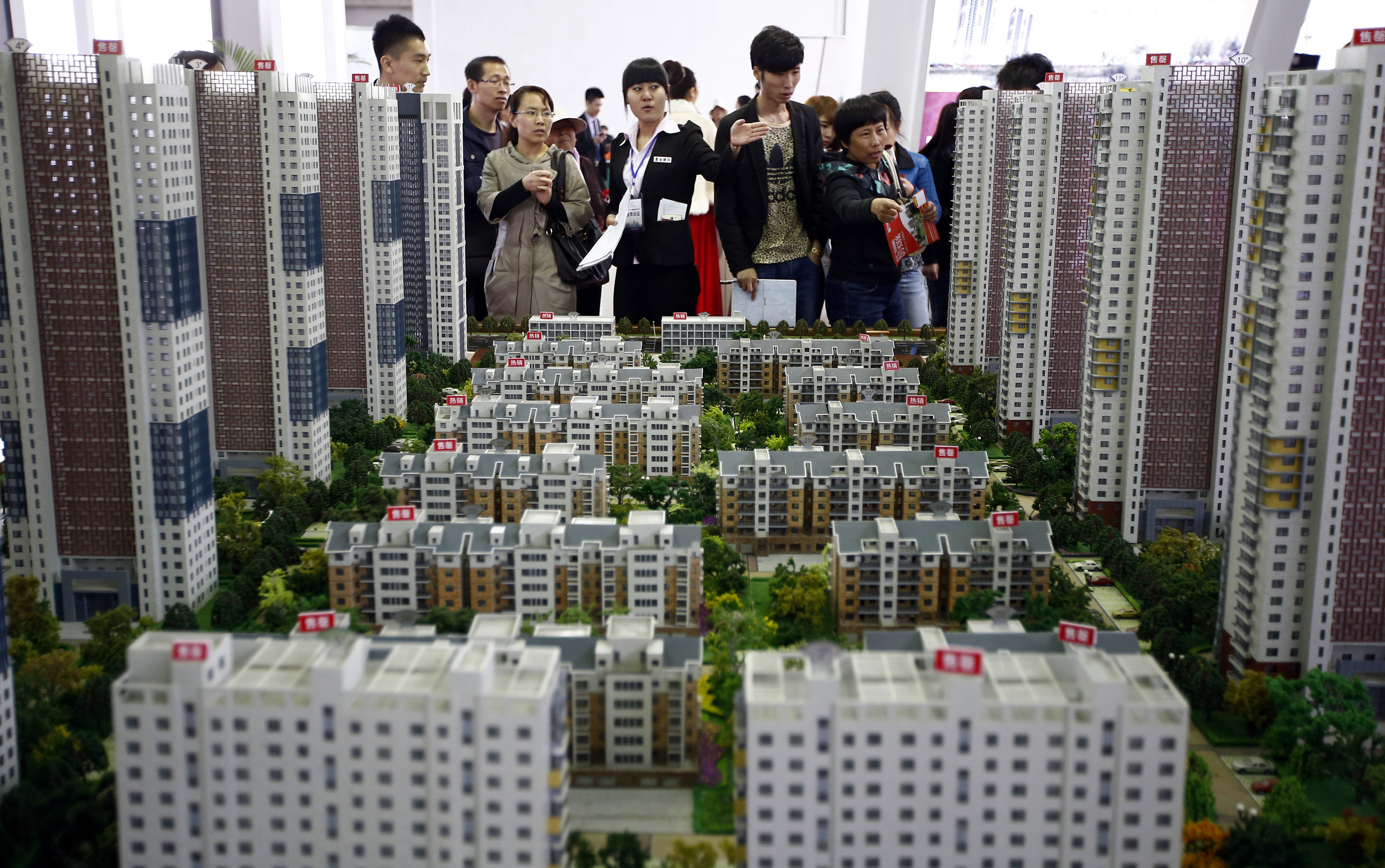 A sales assistant talks to visitors in front of models of apartments at a real estate exhibition in Shenyang, Liaoning province April 17, 2014. China's real estate investment rose 16.8 percent in first three months of 2014 from a year earlier, and revenues from property sales dropped an annual 5.2 percent, the National Bureau of Statistics said on Wednesday. REUTERS/Stringer (CHINA - Tags: REAL ESTATE BUSINESS) CHINA OUT. NO COMMERCIAL OR EDITORIAL SALES IN CHINA - RTR3LM1B