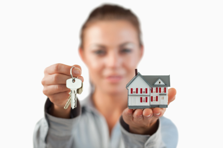 Miniature house and keys being presented by female estate agent