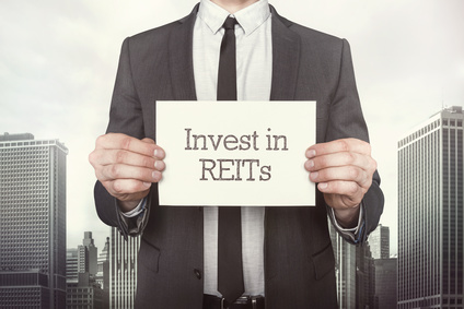 Invest in REITs on paper what businessman is holding on cityscape background
