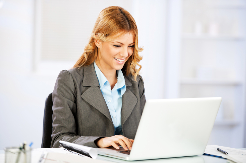 business woman working. Sitting in her office and typing on lap top.