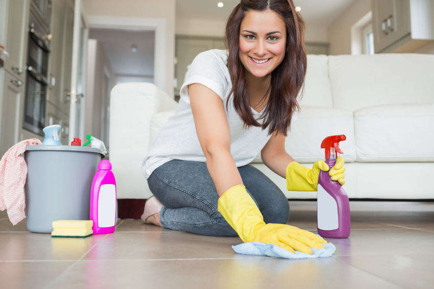 Woman kneeling at the floor cleaning while smiling