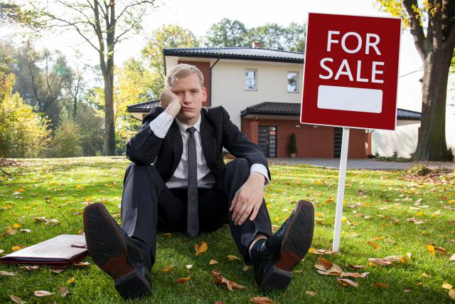 Worried real estate agent and house for sale